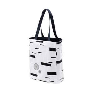 A sturdy, double-sided, reversible bag with side and bottom gussets. The outside is graphite gray and made of recycled cotton, the inside in a thinner patterned lining. It has a pocket with decorative stitches and a narrow pen compartment that provides additional organization. The handles are adapted so that it can be carried in the hand or over the shoulder.